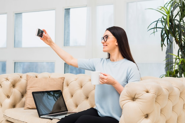 Frau auf der couch, die selfie mit kaffee nimmt