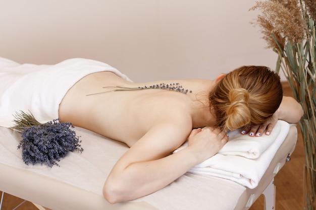 Frau auf der couchmassage mit lavendel. aromatherapie
