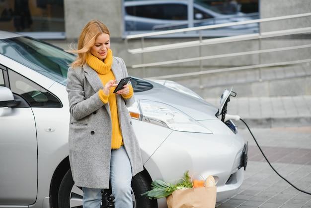 Frau auf der ladestation der elektroautos am tag