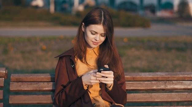 Frau auf der straße auf einer bank mit einem telefon in der handkommunikationsfrischluft.