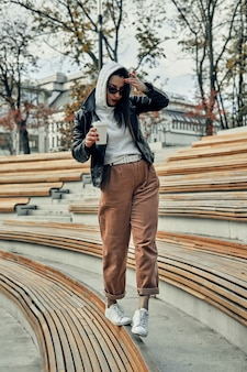 Frau auf der straße mit einem einweg-pappbecher. essen mitnehmen, durch die stadt spazieren.
