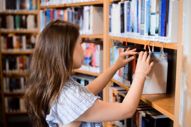 Frau auf der suche nach einem buch in der bibliothek