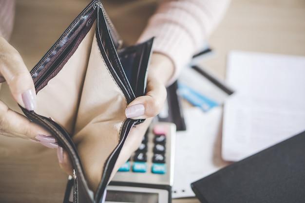 Frau auf der suche nach geld in leeren brieftasche