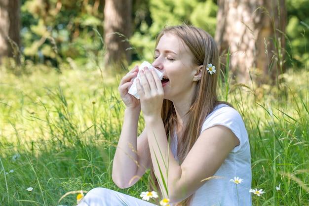 Frau auf der wiese niest, das konzept einer allergie