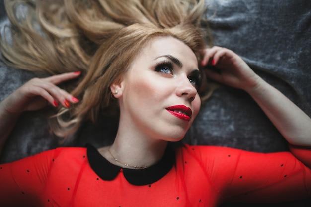 Frau auf einem bett liegend mit geschminkten lippen