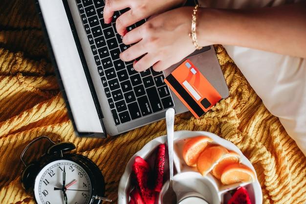 Frau auf einem bett mit hand, die auf laptop-tastatur mit kreditkarte für online-shopping-zahlung tippt