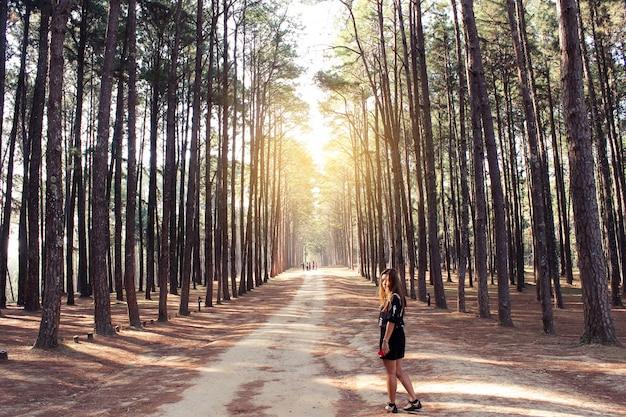Frau auf einem feldweg mit bäumen an den seiten