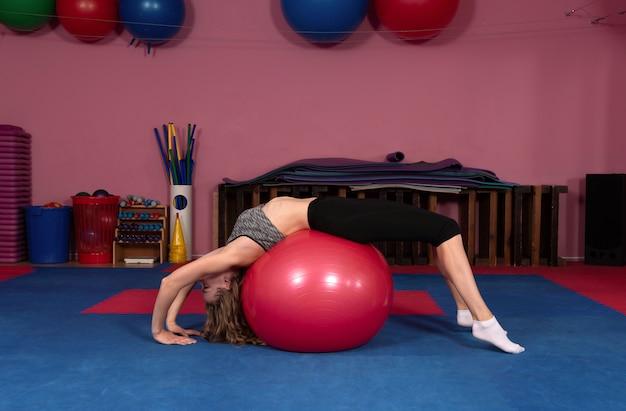 Frau auf einem fitnessball in einer turnhalle
