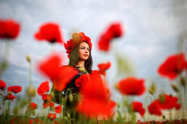 Frau auf einem mohnblumengebiet in einem kleid