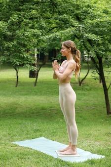 Frau auf einem sadhu-brett meditiert morgens im park