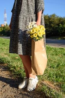 Frau auf einem spaziergang im herbsttag mit einer basteltasche mit schönen blumen. öko-tasche mit chrysanthemenblüten.