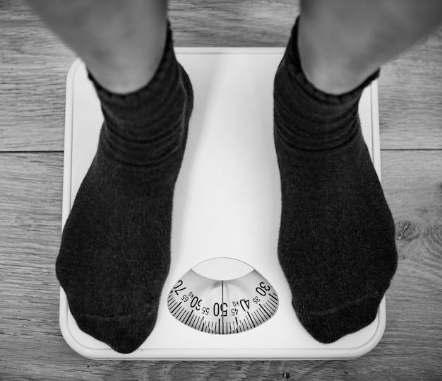 Frau auf einer gewichtsskala