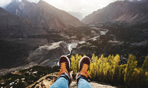 Frau auf einer klippe mit blick auf die berge und ein tal