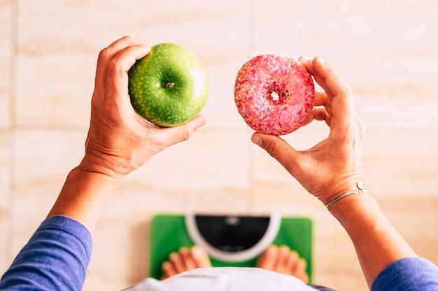 Frau auf einer waage mit einem apfel in der linken hand und einem donut in der rechten hand - sie wählt zwischen diesen beiden arten von lebensmitteln