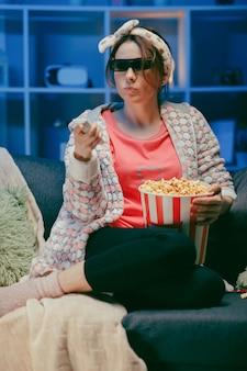 Frau auf einer weichen couch, die popcorn isst, den fernsehbildschirm in 3d-gläsern betrachtend. frau, die popcorn in den 3d-gläsern isst.