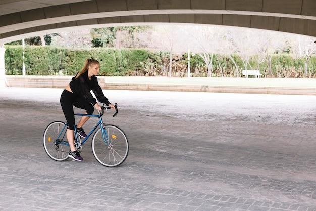 Frau auf fahrrad unter brücke