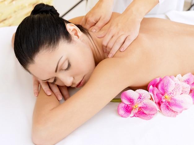 Frau auf gesunde massage des körpers im spa-salon. schönheitsbehandlungskonzept.