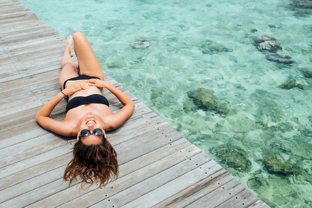 Frau auf hölzernem pier am sonnigen sommertag, draufsicht. junge sexy frau im schwarzen bikini im sommer. sommerstrandurlaubskonzept