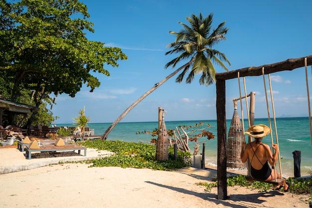 Frau auf ihrem romantischen flitterwochenurlaub lokalisiert auf einem paradiesischen strand mit palmen. teures luxusresort für verheiratete paare und alleinstehende. entspannen sie sich auf einer schaukel. reise nach thailand konzept.
