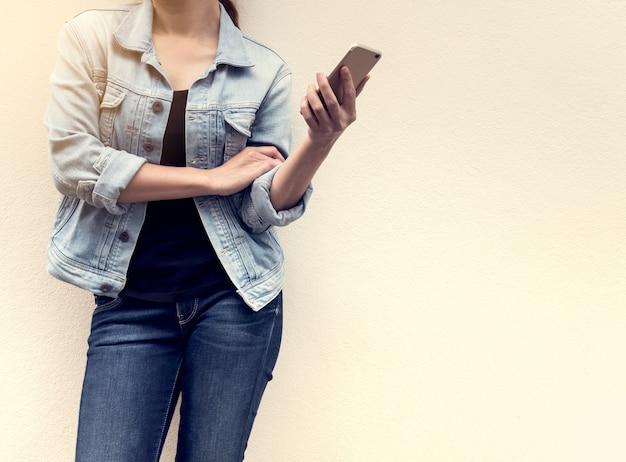 Frau auf jeansmode, die handy hält