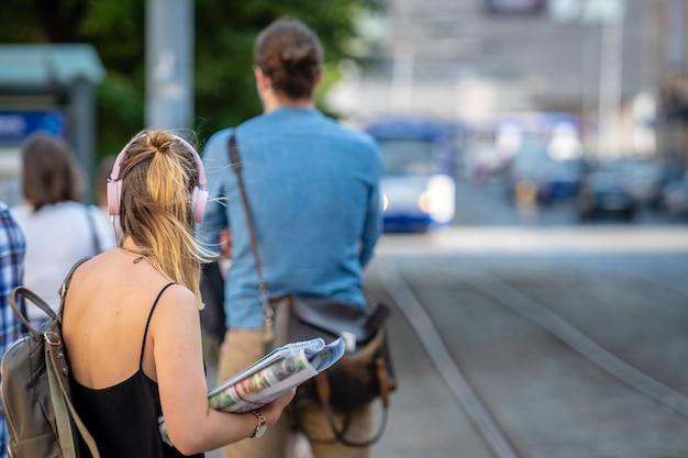 Frau auf kopfhörern hörend musik und auf eine tramhaltestelle wartend.