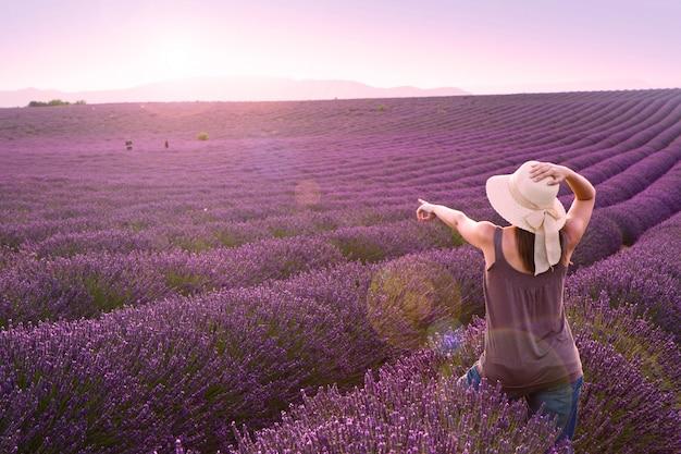 Frau auf lavendelfeld auf rosa sonnenuntergang