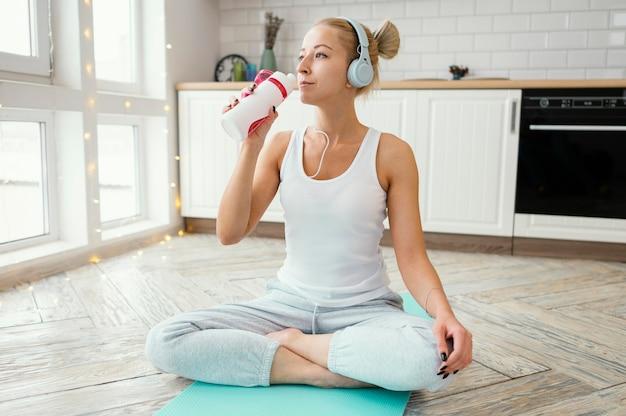 Frau auf matte mit kopfhörern trinkwasser