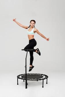 Frau auf rebounder springt hoch und zeigt daumen hoch mit einem lächeln