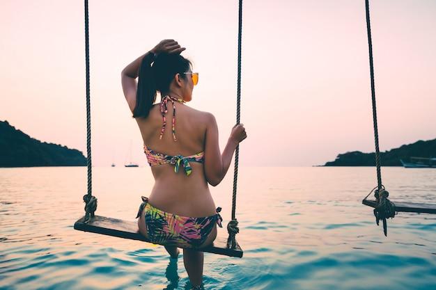 Frau auf schaukel im meer auf tropischer insel