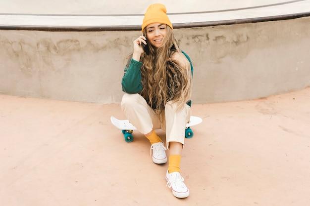 Frau auf skateboard sprechend über telefon