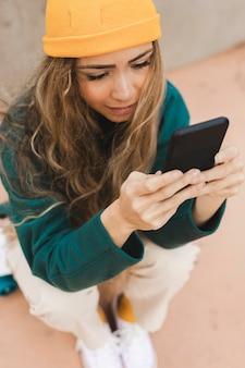 Frau auf skateboard unter verwendung des telefons