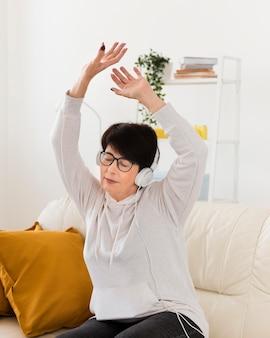 Frau auf sofa, die musik auf kopfhörern hört