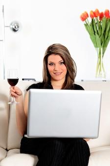 Frau auf sofa mit computer und glas wein
