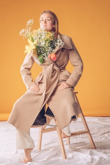 Frau auf strichleiter mit blumenblumenstrauß im mantel