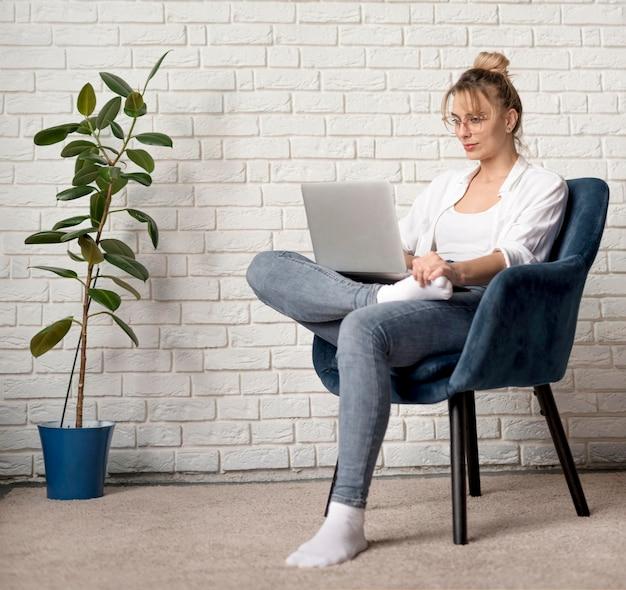 Frau auf stuhl arbeitet am laptop