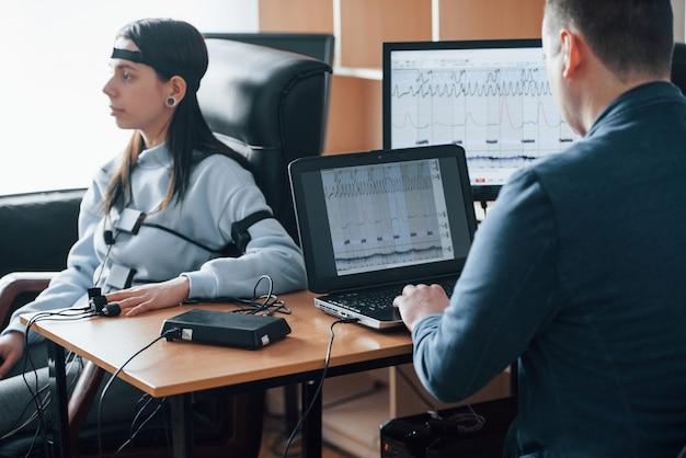 Frau auf treue prüfen. mädchen geht lügendetektor im büro vorbei. fragen stellen. polygraphentest