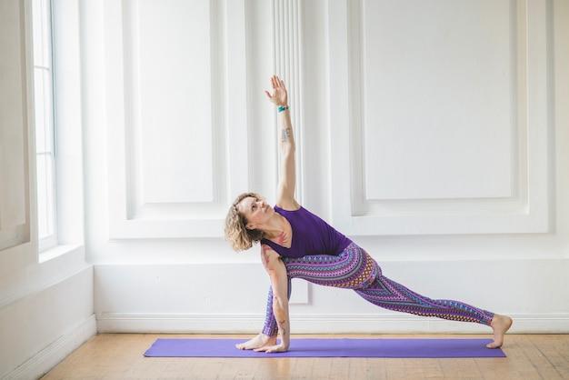 Frau auf yoga matte stretching und meditieren