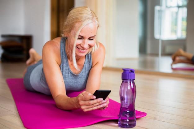 Frau auf yogamatte ihr telefon überprüfend