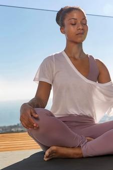 Frau auf yogamatte meditiert