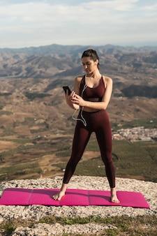Frau auf yogamatte telefon überprüfend