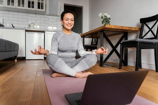 Frau auf yogamatte voller schuss