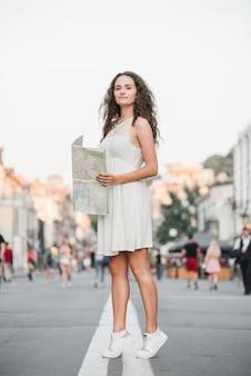Frau auf zehenspitzen mit karte stehen