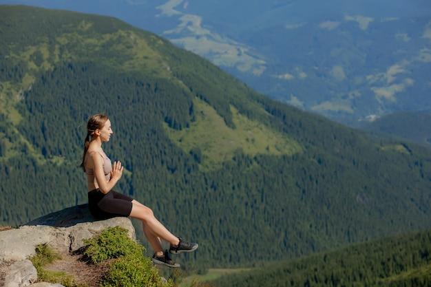 Frau ausgeglichen, meditation und yoga in den bergen praktizierend
