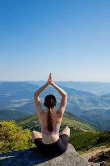 Frau ausgeglichen, meditation und zen-energie-yoga in den bergen praktizierend.