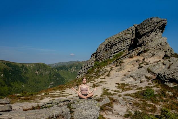 Frau ausgeglichen, meditation und zen-energie-yoga in den bergen praktizierend