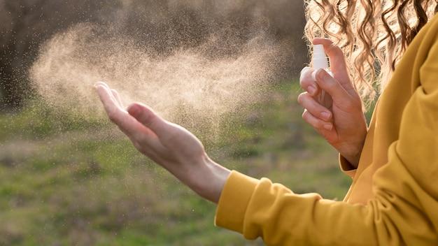 Frau außerhalb mit händedesinfektionsmittel