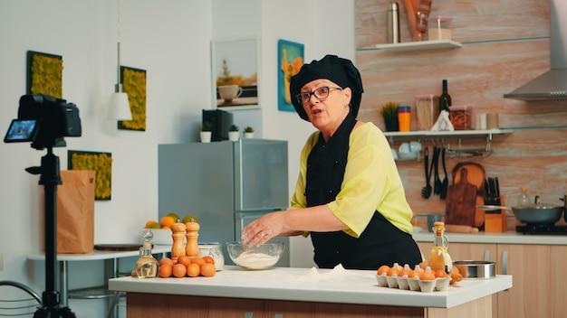 Frau bäcker präsentiert rezept während der aufnahme von tutorial für social media. pensionierter blogger-koch-influencer, der internet-technologie verwendet, um mit digitaler ausrüstung zu kommunizieren, zu fotografieren, zu bloggen in podcasts