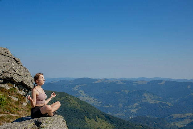 Frau balancierte praktizierende meditation und zen-energie-yoga in den bergen