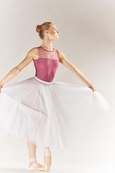Frau ballerina in spitzenschuhen und in einem tutu auf einem hellen hintergrund wirft posierende beine tanzmodell auf