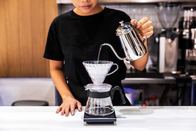 Frau barista beim übergießen von kaffee mit einer alternativen methode namens dripping.